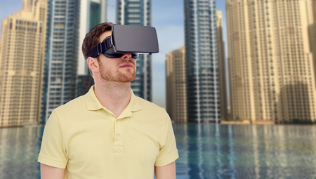 mediated: 3d technology, virtual reality, entertainment and people concept - young man with virtual reality headset or 3d glasses over dubai city infinity edge pool background