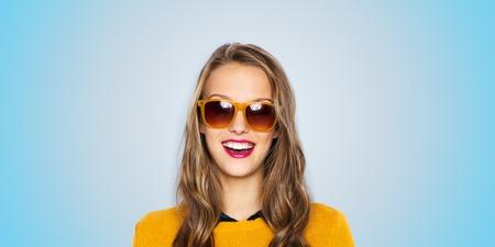 gafas de sol: personas, estilo y concepto de la manera - mujer joven feliz o cara de la muchacha adolescente en gafas de sol sobre fondo azul