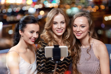 night stick: celebration, friends, bachelorette party, technology and holidays concept - happy women with smartphone selfie stick taking picture at night club Stock Photo