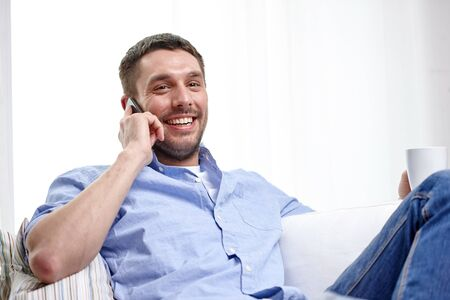 phone conversation: home, technology and internet concept - smiling man with smartphone sitting on couch at home
