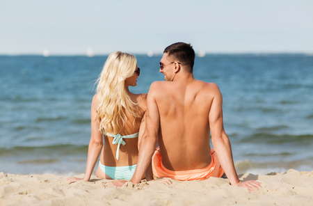 fling: love, travel, tourism, summer and people concept - smiling couple on vacation in swimwear sitting on beach from back