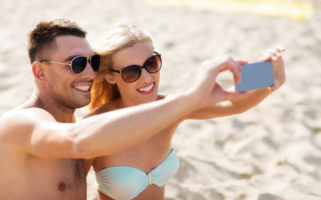 fling: love, travel, tourism, technology and people concept - smiling couple on vacation in swimwear and sunglasses and taking selfie with smartphone on summer beach