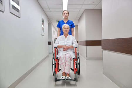 patient in hospital: medicine, age, support, health care and people concept - nurse taking senior woman patient in wheelchair at hospital corridor