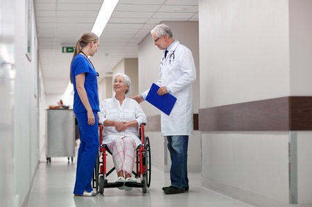patient care: medicine, age, health care and people concept - doctor, nurse and senior woman patient in wheelchair at hospital corridor