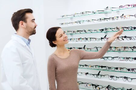 optical: health care, people, eyesight and vision concept - happy woman choosing and showing glasses to optician at optics store