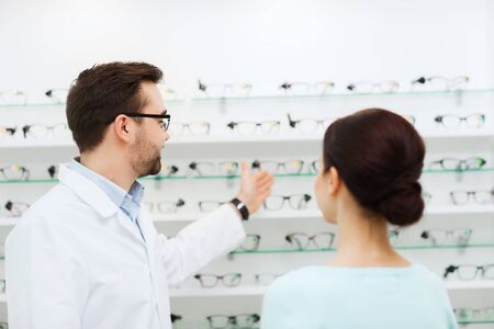 choosing: health care, people, eyesight and vision concept - optician showing glasses to woman at optics store
