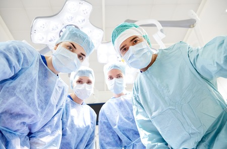 looking into camera: surgery, medicine and people concept - group of surgeons in operating room at hospital looking into camera Stock Photo