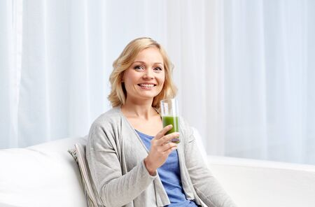 jugo verde: healthy eating, vegetarian food, dieting, detox and people concept - smiling middle aged woman drinking green fresh vegetable juice or smoothie from glass at home