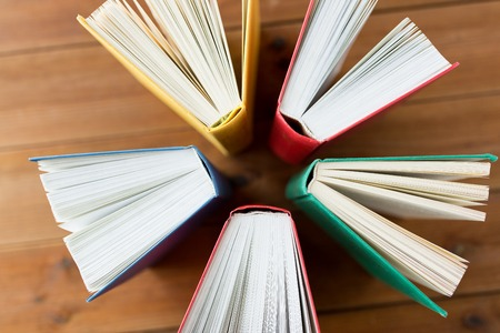 storybook: education, school, literature, reading and knowledge concept - close up of books on wooden table Stock Photo