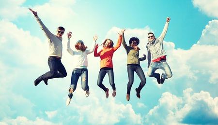 personas saltando: las personas, la libertad, la felicidad y el concepto de adolescentes - grupo de amigos felices con gafas de sol salto de altura sobre el cielo azul y las nubes de fondo Foto de archivo
