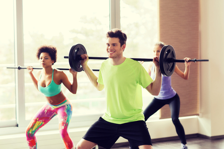 pesas: fitness, sport, training, gym and lifestyle concept - group of people exercising with barbell and bars in gym Foto de archivo