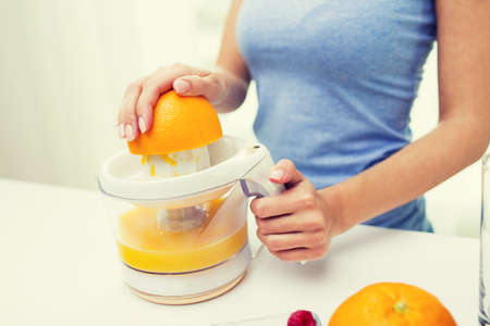 juice squeezer: healthy eating, vegetarian food, dieting and people concept - close up of woman with squeezer squeezing orange juice at home