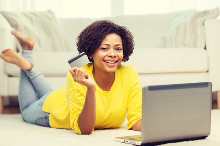emoney: people, internet bank, online shopping, technology and e-money concept - happy african american young woman lying on floor with laptop computer and credit card at home Stock Photo