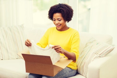 delivery box: people, delivery, commerce, shipping and postal service concept - happy african american young woman taking clothes out of cardboard box or parcel at home Stock Photo