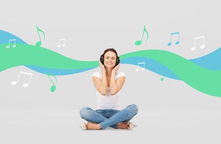 personas escuchando: la tecnología, la música y el concepto de la felicidad - mujer joven o una chica adolescente en los auriculares sobre fondo gris y la onda musical con notas sonriendo