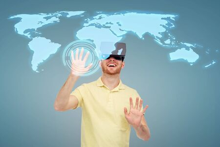 mediated: 3d technology, virtual reality, entertainment and people concept - happy young man with virtual reality headset or 3d glasses playing game over blue background and world map Stock Photo
