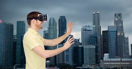 mediated: 3d technology, virtual reality, travel, entertainment and people concept - happy young man with virtual reality headset or 3d glasses playing game over singapore city skyscrapers background