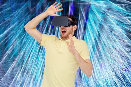 entertainment background: 3d technology, virtual reality, entertainment and people concept - happy young man with virtual reality headset or 3d glasses playing game over spiral neon lights background