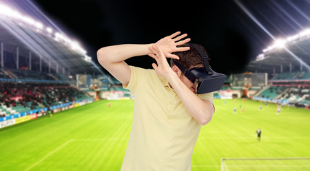 mediated: 3d technology, virtual reality, sport, entertainment and people concept - happy young man with virtual reality headset or 3d glasses playing game over football field on stadium background
