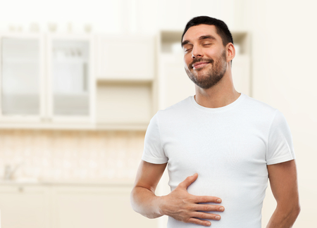 SATISFIED: eating, satisfaction and people concept - happy full man touching his tummy over kitchen background