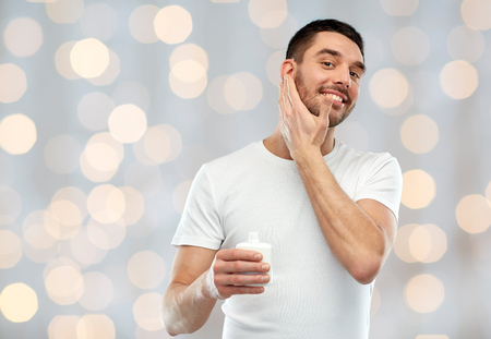 aftershave: beauty, skin care, body care and people concept - smiling young man applying cream or lotion to face over holidays lights background Stock Photo
