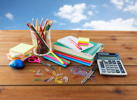 office supplies: education, school supplies, art, creativity and object concept - close up of stationery on wooden table over blue sky and clouds background
