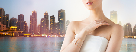 wristlet: glamour, beauty, jewelry and luxury concept - close up of beautiful woman with golden ring and bracelet over singapore city skyscrapers background