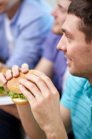 eating fast food: fast food, unhealthy eating, people and junk-food - close up of happy friends eating hamburgers at home Stock Photo