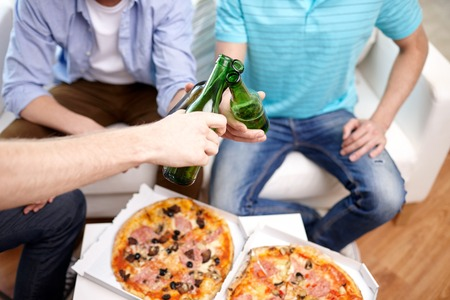 clinking: friendship, alcohol, people, celebration and holidays concept - close up of male hands clinking beer bottles and eating pizza at home