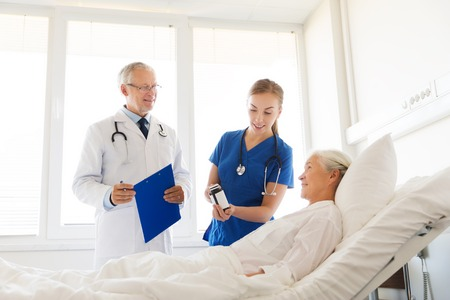 health care and medicine: medicine, age, health care and people concept - doctor and nurse showing medicine to senior woman at hospital ward Stock Photo