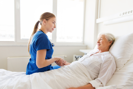 medicine, age, support, health care and people concept - doctor or nurse visiting and cheering senior woman lying in bed at hospital ward Stock Photo