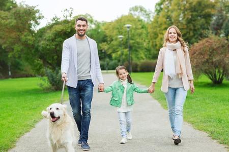 家族、ペット、家畜、人コンセプト - 夏の公園を歩いてラブラドル ・ レトリーバー犬犬と幸せな家庭