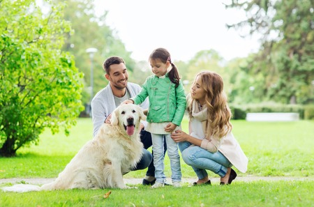 family, pet, domestic animal and people concept - happy family with labrador retriever dog on walk in summer park Banque d'images