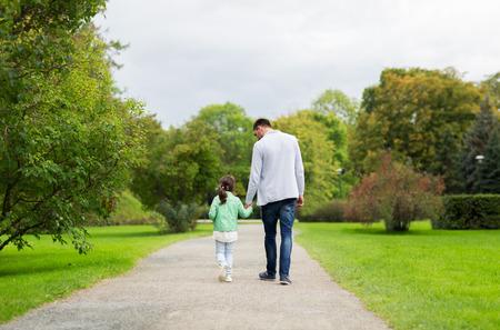 la familia, la maternidad, la paternidad, la adopción y la gente conceptuales - padre feliz y niña caminando en el parque de verano