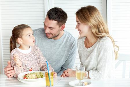 Familie, Elternschaft, Kommunikation und Menschen Konzept - glückliche Mutter, Vater und kleine Mädchen Pasta zum Abendessen zu essen und sprechen im Restaurant oder Café