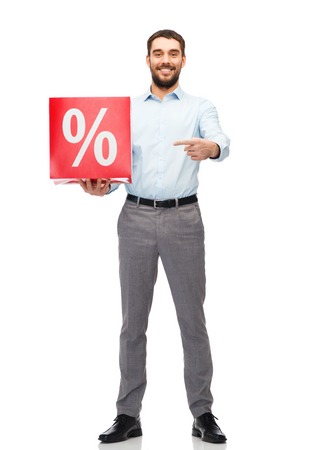 percentage sign: people, sale, shopping, discount and holidays concept - smiling man holding and pointing finger to red percentage sign Stock Photo