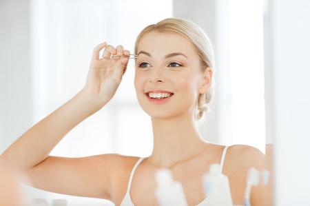pinzas: la belleza y el concepto de la gente - mujer joven con pinzas de depilación con pinzas de cejas y mirando sonriente al espejo en el baño casa Foto de archivo