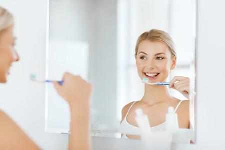 mirror face: health care, dental hygiene, people and beauty concept - smiling young woman with toothbrush cleaning teeth and looking to mirror at home bathroom
