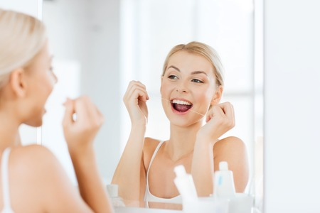 home health care: health care, dental hygiene, people and beauty concept - smiling young woman with floss cleaning teeth and looking to mirror at home bathroom