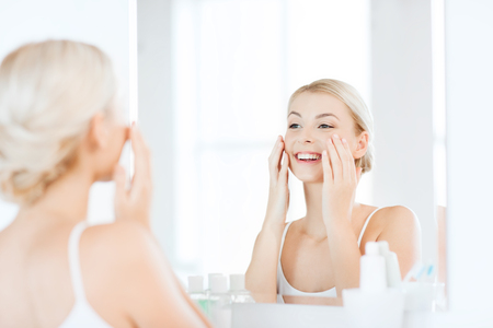 Beauté, soins de la peau et les gens concept - jeune femme souriante d'appliquer la crème sur le visage et regardant au miroir à la maison salle de bain Banque d'images - 61638945