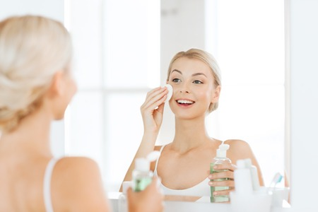 cotton: beauty, skin care and people concept - smiling young woman applying lotion to cotton disc for washing her face at bathroom
