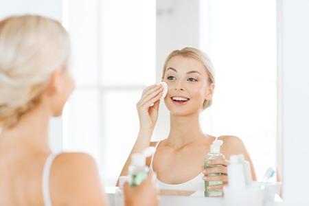 Schoonheid, huidverzorging en mensen concept - lachende jonge vrouw aanbrengen van lotion op katoenen schijf voor het wassen van haar gezicht op de badkamer