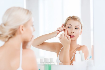 bad hygiene: beauty, hygiene, skin problem and people concept - young woman looking to mirror and squeezing pimple at home bathroom Stock Photo