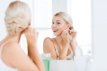 persona feliz: Belleza, joyas y concepto de la gente - sonriente joven mujer tratando de pendiente de diamantes y mirando a espejo en casa baño Foto de archivo