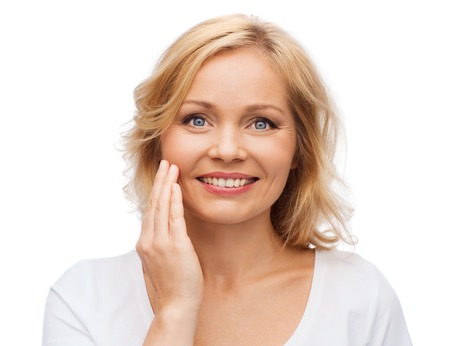 touching face: beauty, people and skincare concept - smiling woman in white shirt touching face