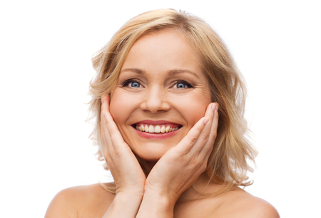 touching face: beauty, people and skincare concept - smiling woman with bare shoulders touching face Stock Photo