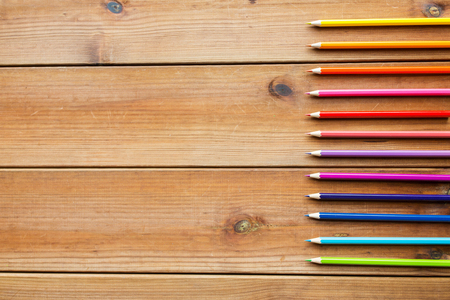 color pencils: art, color, drawing, creativity and object concept - close up of crayons or color pencils on wooden table