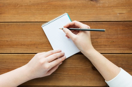 hand writing: education, business and people concept - close up of woman or student with pencil writing to notepad on wooden table Stock Photo