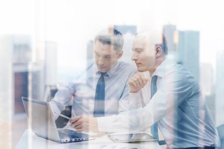 비즈니스, 기술 및 사무실 개념 - 랩톱, tablet pc 컴퓨터 및 사무실에서 토론을 갖는 논문 두 기업인
