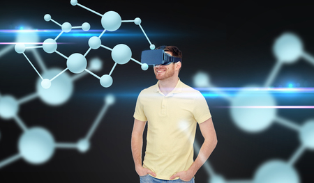 mediated: 3d technology, virtual reality, biology, entertainment and people concept - happy young man in virtual reality headset or 3d glasses looking at molecules over black background Stock Photo